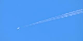 Szybki samolot i dymiący lot wlec na niebieskim niebie Zdjęcie Royalty Free