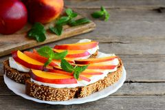 Szybkie kanapki z kremowym serem, świeżymi nektarynami i mennicą, na porcja talerzu i na rocznika drewnianym tle Zdjęcie Stock