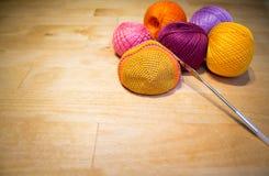 Szydełkować w toku i kolorowe bawełniane niciane piłki na drewnianym tle z przestrzenią Obrazy Royalty Free