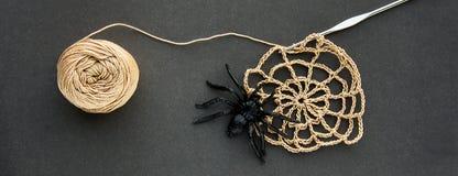 Szydełkująca pajęczyna z czarną gumową pająka, szydełkowej i bawełnianej przędzy piłką nici na czerń papieru tle, Ciemny Hallowee zdjęcia royalty free