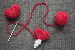 Szydełkujący czerwoni serca na grunge desce Fotografia Stock