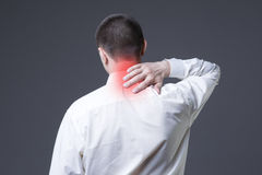 Szyja ból, mężczyzna z backache na szarym tle obrazy royalty free
