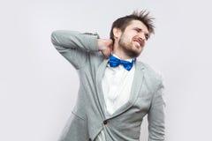 Szyja ból Portret przystojny brodaty biznesmen w przypadkowym siwieje kostium, błękitny łęku krawata mienie i pozycja i jego bole obraz royalty free