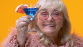 Szyk starzejąca się dama pokazuje błękitnego koktajlu szkło w ręce, elegancka babcia relaksuje zdjęcie wideo