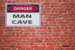 Szyldowa niebezpieczeństwo mężczyzny jama na czerwonej cegle wal zdjęcia stock