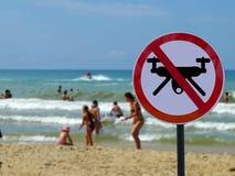 Szyldowi zakazów trutnie w tle plaża z turystów ludźmi zdjęcia royalty free