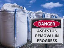 Szyldowy azbestowy usunięcie w toku i sterta duże torby azbest fotografia stock