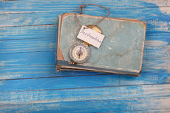 Szyldowy miejsce przeznaczenia i kompas na starej książce - rocznika styl Fotografia Stock