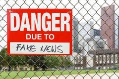Szyldowy niebezpieczeństwo należny sfałszowany wiadomości obwieszenie na ogrodzeniu fotografia royalty free