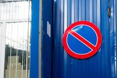 Szyldowy zabrania parking samochody na błękitnej ścianie i biali wi Fotografia Stock