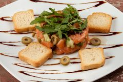 Tártaro de color salmón con el aguacate, el pepino, las aceitunas y el arugula Foto de archivo libre de regalías