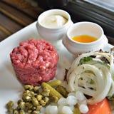 Tártaro do bife servido com vegetais e especiarias Fotos de Stock