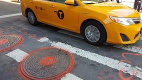 Táxi amarelo de NYC que conduz na estrada com tampas do manhaole foto de stock