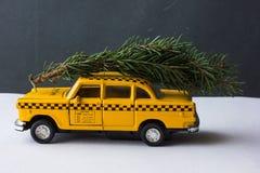 Táxi amarelo do brinquedo em um tronco de árvore Natal Imagens de Stock