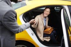 Táxi de ajuda da licença da jovem mulher do cavalheiro imagem de stock royalty free