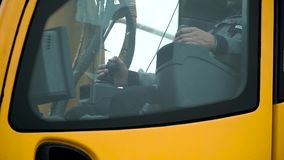Táxi de motoristas de um funcionamento amarelo do guindaste em um canteiro de obras grampo Trabalhe o motorista do braço do guind filme