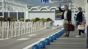 Táxi de saudação da viagem de negócios, do homem e da mulher perto do aeroporto, viajando, viagem vídeos de arquivo