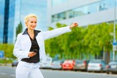 Táxi de travamento de sorriso da mulher de negócio Imagem de Stock