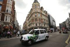 Táxi típico de Londres nas ruas da capital do ` s de Inglaterra Imagem de Stock Royalty Free
