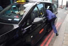 Táxi típico de Londres nas ruas da capital do ` s de Inglaterra Foto de Stock