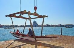 Táxi tradicional da água no estilingue aproximadamente a ser abaixado no canal de Giudecca o redentore visível no fundo Imagem de Stock