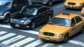 Táxis de táxi e o outro tráfego em uma rua ocupada de NYC vídeos de arquivo