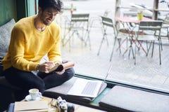 Tâche accomplissante de jeune redacteur publicitaire masculin créatif traduisant le texte Photographie stock libre de droits