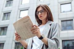 Tägliche Nachrichten Junge Dame in den Brillen, die auf der beteiligten Nahaufnahme der Stadtstraßenlesezeitung stehen stockbild