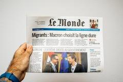 Täcker den läs- Le Mondefranskan för man tidningen med billyktan och p Arkivfoto