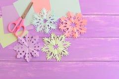 Täcker scissors pappers- snöflingor för rosa färger, för gräsplan, för blått och för lilor, färgat papper, på träbakgrund med kop Royaltyfri Fotografi