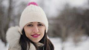 Täcker ståenden för unga kvinnor för Closeupbrunetthår med rosa kanter i beiga ner och hatten som ler i snöig Central Park lager videofilmer
