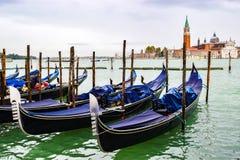 Täckte gondoler som anslutas på vatten mellan träförtöja poler i Venedig, Italien Kyrka av San Giorgio Maggiore i bakgrund royaltyfria foton