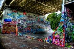 Täckte grafitti åka skridskor det halva röret royaltyfri bild