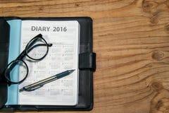 Tägliches Planerbuch im schwarzen ledernen Kasten mit Gläsern und Stift stockfotos