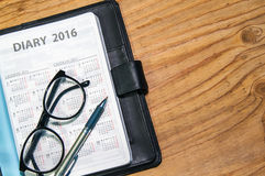 Tägliches Planerbuch im schwarzen ledernen Kasten mit Gläsern und Stift Lizenzfreies Stockbild