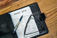 Tägliches Planerbuch im schwarzen ledernen Kasten mit Gläsern und Stift Lizenzfreie Stockfotos