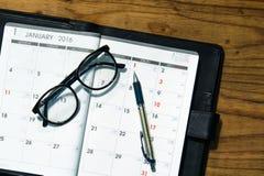 Tägliches Planerbuch im schwarzen ledernen Kasten mit Gläsern und Stift an lizenzfreies stockfoto