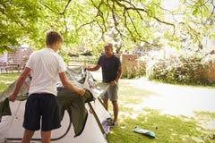 Tält för faderAnd Teenage Son uppställning på campa tur arkivbilder