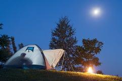 Tält i skymning med den horisontalmånen och brand Royaltyfri Foto
