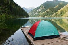 Tält med en sikt av sjön i bergen Fotografering för Bildbyråer