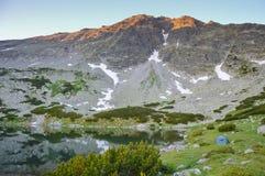 Tält nära sjön i berg Arkivfoto