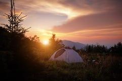 Tält på berget med signalljuset av soluppgång Royaltyfri Bild