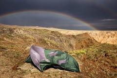 Tält som är brutet vid stark vind och en regnbåge royaltyfria bilder