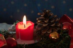 Tänd stearinljus i en adventgarnering med kottar och struntsaker Arkivfoton