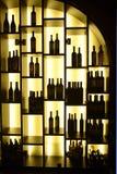 Tända hyllor med rött vinflaskor, affär Arkivbild