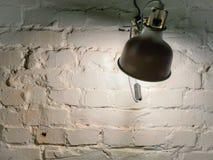Tända lampan på en vit tegelstenvägg arkivfoto