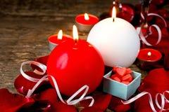 Tända röda och vitstearinljus i rosa kronblad, kakor i en gåvaask på den gamla träbakgrunden, selektiv fokus Arkivfoto