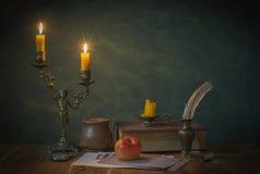Tända stearinljus och böcker arkivbild