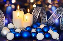 Tända stearinljus och blåa vita julgrangarneringar på arkivfoto