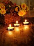 Tända stearinljus och en vide- korg med en pumpa och blommor i bakgrunden Arkivbild
